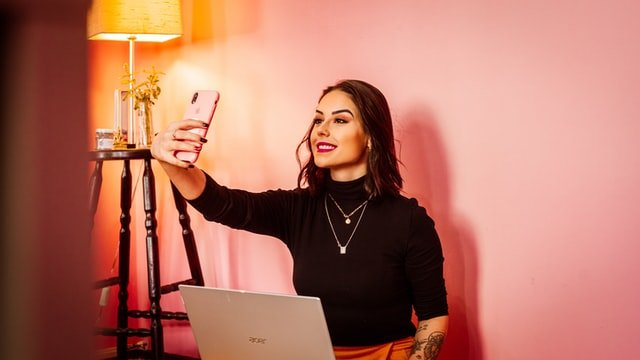 woman taking selfie as a way to make money selling photos of herself